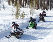 Snowmobilers enjoying their sleds along a groomed path