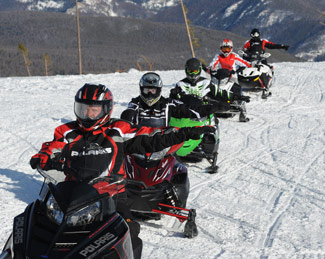 Snowmobilers following basic hand signals